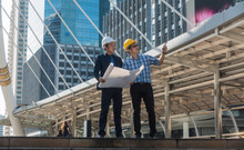 Full Length Of Engineer And Businessman Discussing Over Blueprint While Standing In City
