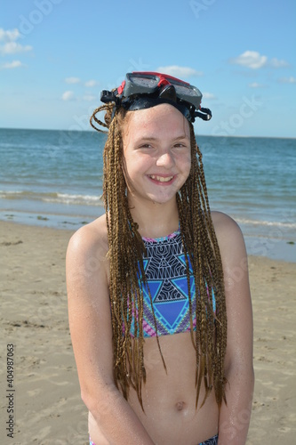 Obraz Portrait Of Smiling Girl Standing At Beach - fototapety do salonu
