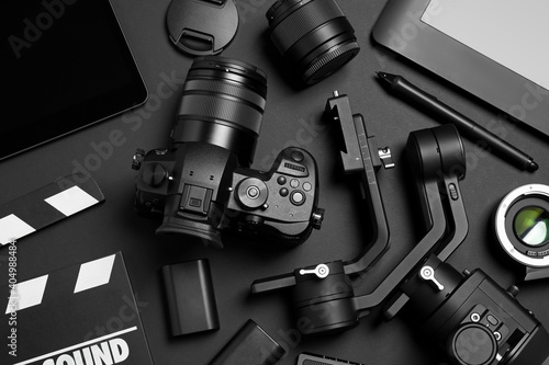 Fototapeta Flat lay composition with camera and video production equipment on black background obraz na płótnie