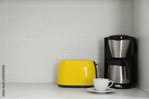 Fotografering Modern yellow toaster and coffeemaker on countertop in kitchen