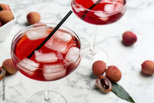 Delicious lychee cocktail and fresh fruits on white marble table, closeup. Space for text