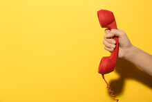 Closeup View Of Woman Holding Red Corded Telephone Handset On Yellow Background, Space For Text. Hotline Concept