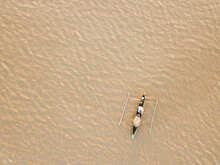 Aerial View Of A Fishing Pirogue In Brownish Muddy Water