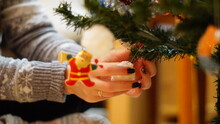 Midsection Of Woman Decorating Christmas Tree At Home
