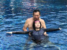 High Angle Portrait Of Grandfather Teaching Swimming To Granddaughter In Pool