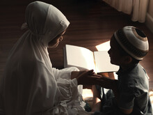 Low Key Image Of Religious Asian Muslim Kids Slam Or Greeting,learn  The Quran And Study Islam After Pray To God At Home .Sunset Light Shining Through The Window.Peaceful And Marvelous Warm Climate.