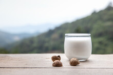 Macadamia Milk In A Glass With Bark On Wooden Floor And Look Mountain Hill View Is Background.