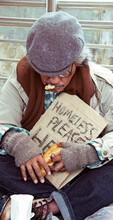 Homeless Man Eating Bread On Street