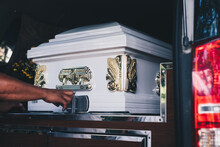Close Up Of A Casket Loaded In A Hearse Or  Funeral Plan Car Or Coach For The Funeral Procession. Selective Focus.