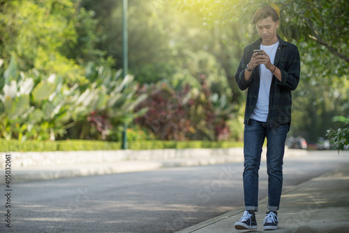 Stampa su Tela Full Length Of Young Man Using Phone While Standing On Sidewalk