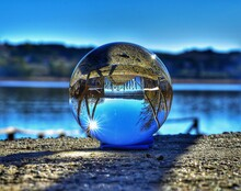 Close-up Of Crystal Ball By Lake With Reflection
