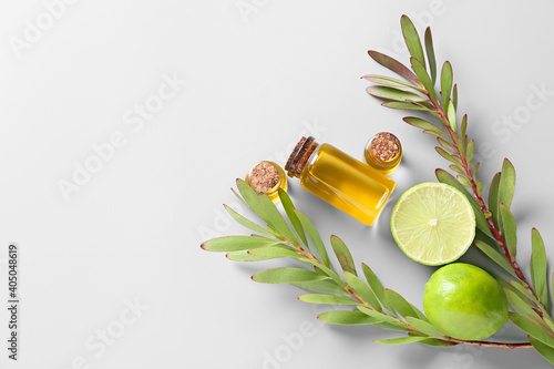 Bottles with citrus essential oil on light background