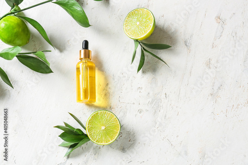 Bottle with citrus essential oil on light background