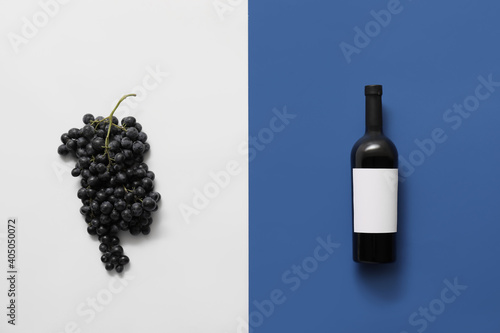 Fototapeta Bottle of wine with blank label and grapes on color background obraz