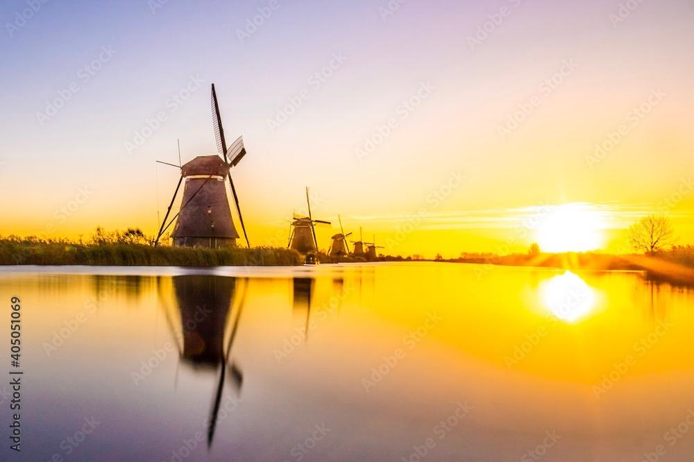 Leinwandbild Motiv - jan guit/EyeEm : Traditional Windmills By Lake Against Sky During Sunset