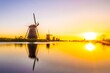 Leinwandbild Motiv Traditional Windmills By Lake Against Sky During Sunset