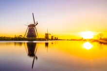 Traditional Windmills By Lake Against Sky During Sunset