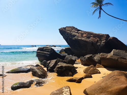 Obraz Rocks On Beach Against Clear Blue Sky - fototapety do salonu