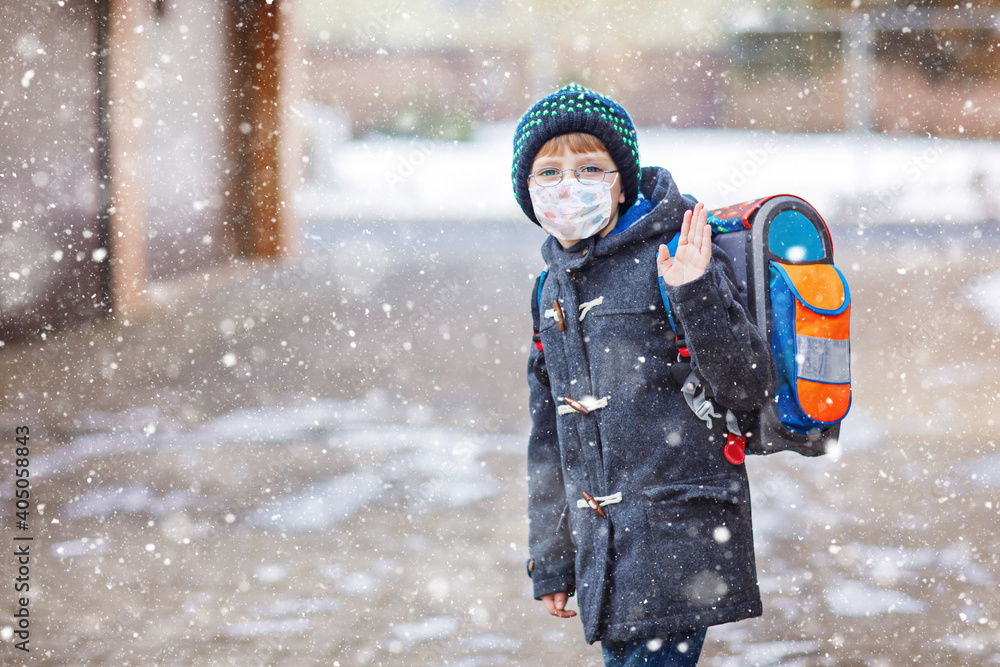Fototapeta Little kid boy with glasses wearing medical mask on the way to school after lockdown. Child backpack satchel. Schoolkid on winter day with warm clothes. Quarantine time during corona pandemic disease