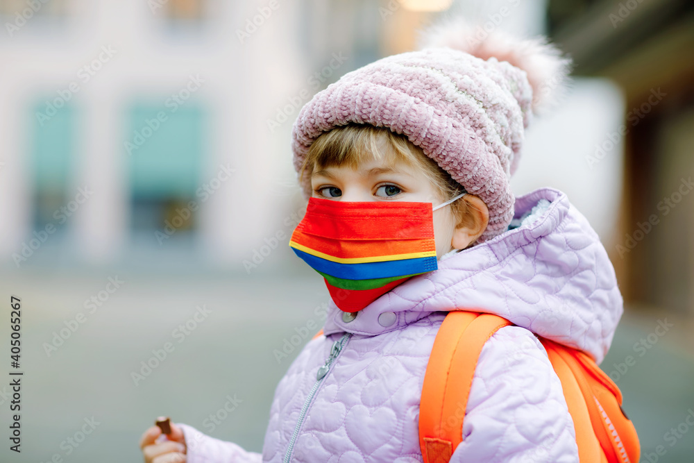 Fototapeta Little kid girl wearing medical mask on the way to kindergarten, playschool or nursery. Child with backpack satchel on cold day with warm clothes. Lockdown and quarantine time during corona pandemic