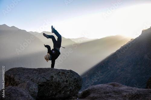 Foto Sujeto parado sobre su mano en el amanecer de Marcahuasi, Lima, Perú