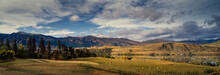 Panorama Of Farm And Snow Capped Mountain Range Surrounding Lake Hayes And Round Hay Bales In Field