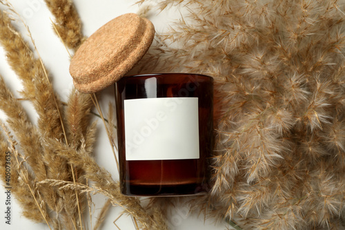 Scented candle and reed on white background