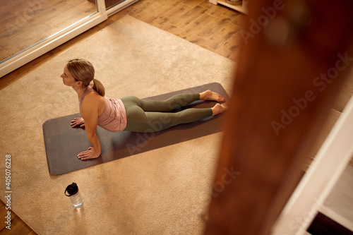 Obraz Above view of athletic woman doing Yoga exercises in her living room. - fototapety do salonu
