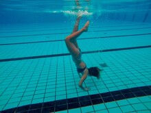 Woman Doing Handstand While Swimming In Pool