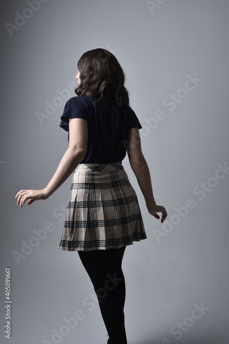 Foto Close up portrait of pretty brunette woman wearing tartan skirt and blouse