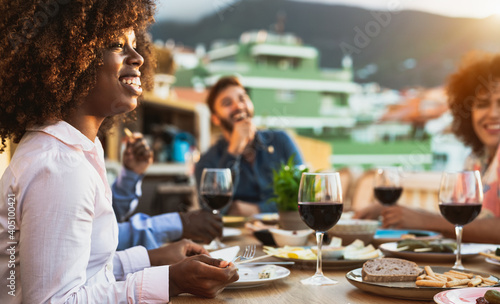 Fotografering Young multiracial friends doing appetizer and drinking red wine on house patio d