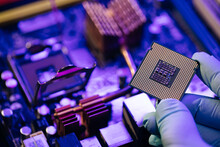Engineer Showing A Computer Microchip On Motherboard Background. Electronic Circuit Board With Processor