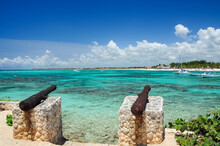 Probably, This Old Cannons, Were Part Of An Old Ship That Wrecked In The Area. Akumal, Quintana Roo, México.  It Can Be Seen The Pristine Waters Of Akumal Beach, And Some Sailboats Docked On The Shore