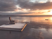 Scenic View Of Sea With Chair On Wooden Raft Against Sky During Sunset