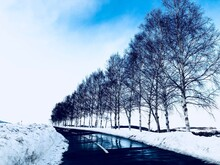 Snow Covered Bridge Over Canal Against Sky