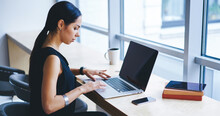 Serious Female Entrepreneur Working On Netbook In Workspace