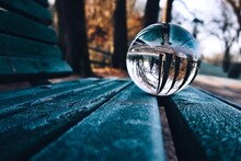 Close-up Of Crystal Ball On Wooden Bench