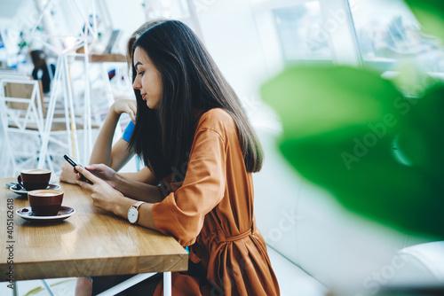 Fotografie, Obraz Pensive women with smartphone resting in cafeteria