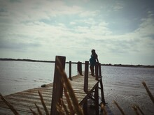 Pregnant Woman Standing On Pier Over Lake Against Cloudy Sky