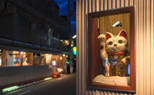 """Early Evening View Of A Maneki-neko, A Japanese Symbol Of Good Fortune, In A Display Case At The Front Entrance Of A Store (translation: Collar Means """"luck"""", Coins Mean """"ten Million Gold Pieces"""")"""