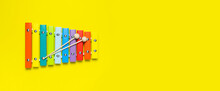 Multicolored Wooden Xylophone And Shock Sticks On Bright Yellow Background Flat Lay Top View Copy Space. Wooden Children's Musical Toy Baby Musical Instrument Colors Of Rainbow. Kids Natural Eco Toys