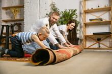 Young Couple, Family Doing Apartment Repair Together Themselves. Mother, Father And Son Doing Home Makeover Or Renovation. Concept Of Relations, Moving, Love. Rolling The Carpet On The Floor