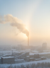 The Chimney Of A Steaming Power Plant Emerges From The Back Fog. The Chimney Of The Power Plant Rises Above The Surrounding Fog. Energy. Heating Plant In Operation.