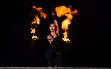 High Energy Firedancer. Sensual Firedancer Twirl Flaming Baton In Darkness. Fire Performance. Art Show. Baton Twirling. Holiday Celebration. Night Party. Living In Dancing