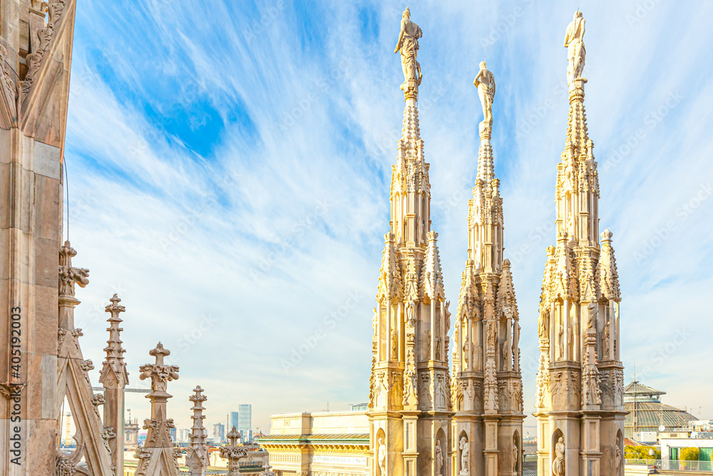 Fototapeta Roof of Milan Cathedral Duomo di Milano with Gothic spires and white marble statues. Top tourist attraction on piazza in Milan, Lombardia, Italy. Wide angle view of old Gothic architecture and art.