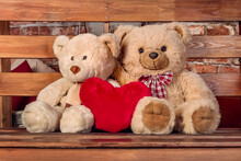 Two Teddy Bears Are Sitting On A Bench Next To A Soft Toy Heart