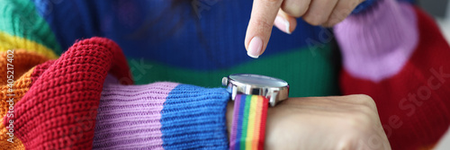 Fotografering Woman in an lgbt sweater points her finger at clock face