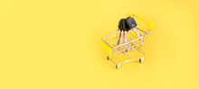 Mini Cart With Keys On A Yellow Background. The Concept Of Buying Or Renting A House, Apartment. Copy Space For Text. Baner. View From Above