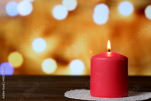 Burning thick pink aromatic candle on white openwork paper napkin on wooden table, yellow bokeh lights background closeup view selective focus. Love, Valentine's, women's day, romantic concept