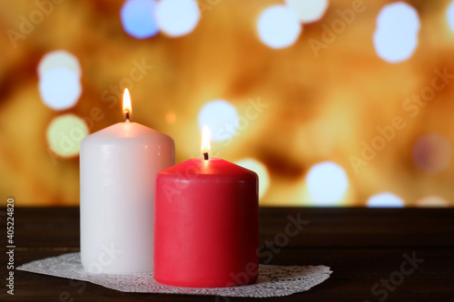 White and pink burning aromatic candles on white openwork paper napkin on wooden table, yellow bokeh lights background closeup view selective focus. Love, Valentine's, women's day, romantic concept